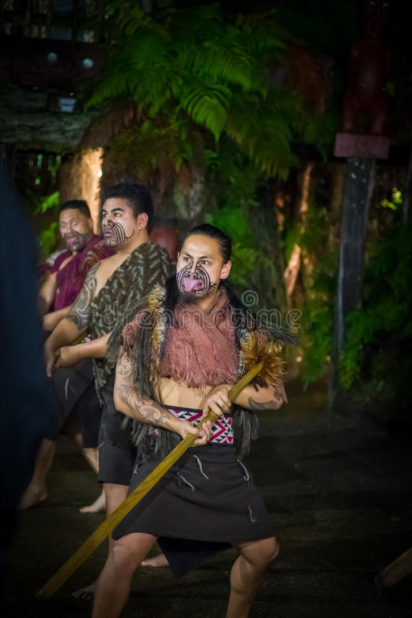 NORTH ISLAND, NEW ZEALAND- MAY 17, 2017: Maori men screaming with traditionally tatooed face in traditional dress at. Maori Culture doing a traditional dance stock image