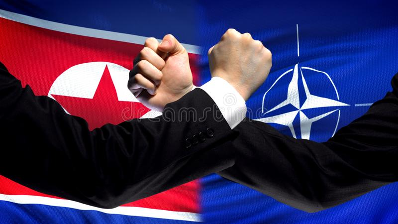 North Korea vs NATO confrontation, interests conflict, fists on flag background royalty free stock images