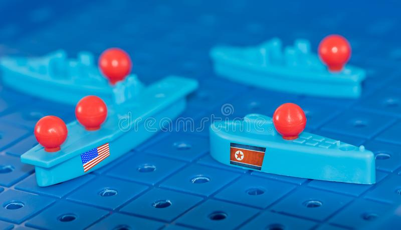 North Korean submarine and a us aircraft carrier. A collision on a toy Board battleship North Korean submarine and a us aircraft carrier royalty free stock photos
