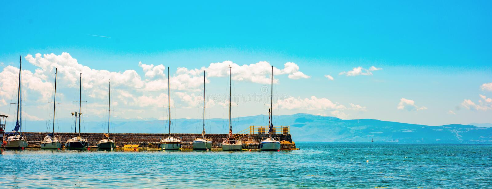 North macedonia. Ohrid. Long pier with different sailboats and mountines on background stock photography