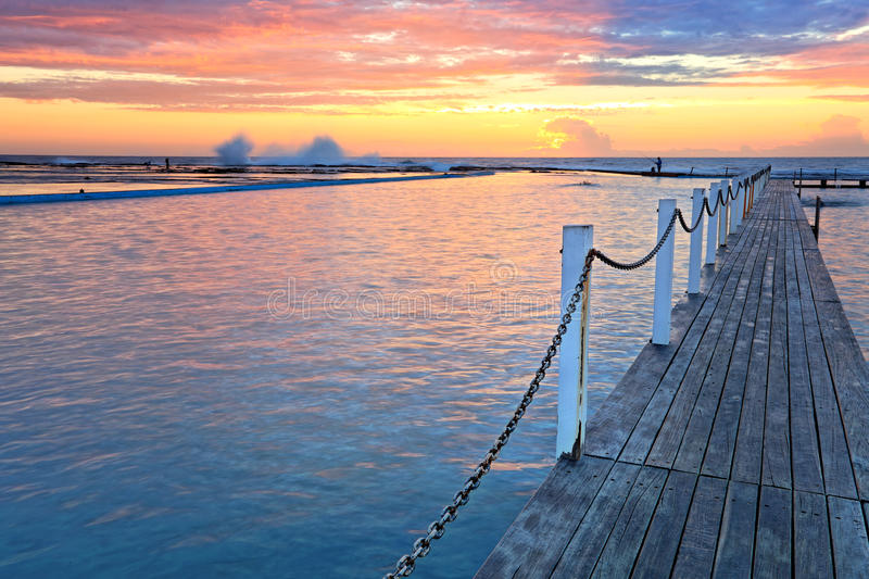 North Narrabeen Ocean Rock Pools at sunrise. The view across Narrabeen Ocean Rock Pools and the rock shelf beyond on a spectacular sunrise morning. The waters royalty free stock photos