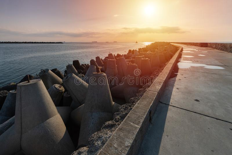 North pier with breakwaters, sunset seascape. Modern lighthouse in sunlight. Tetrapods along edges of pier. Beautiful evening royalty free stock photos