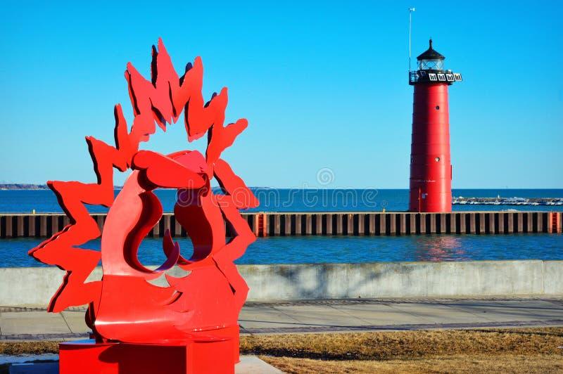 North Pier Lighthouse Kenosha, Wisconsin. This is the red North pier lighthouse with some modern art along Lake Michigan in Kenosha, Wisconsin. It was built in royalty free stock photography