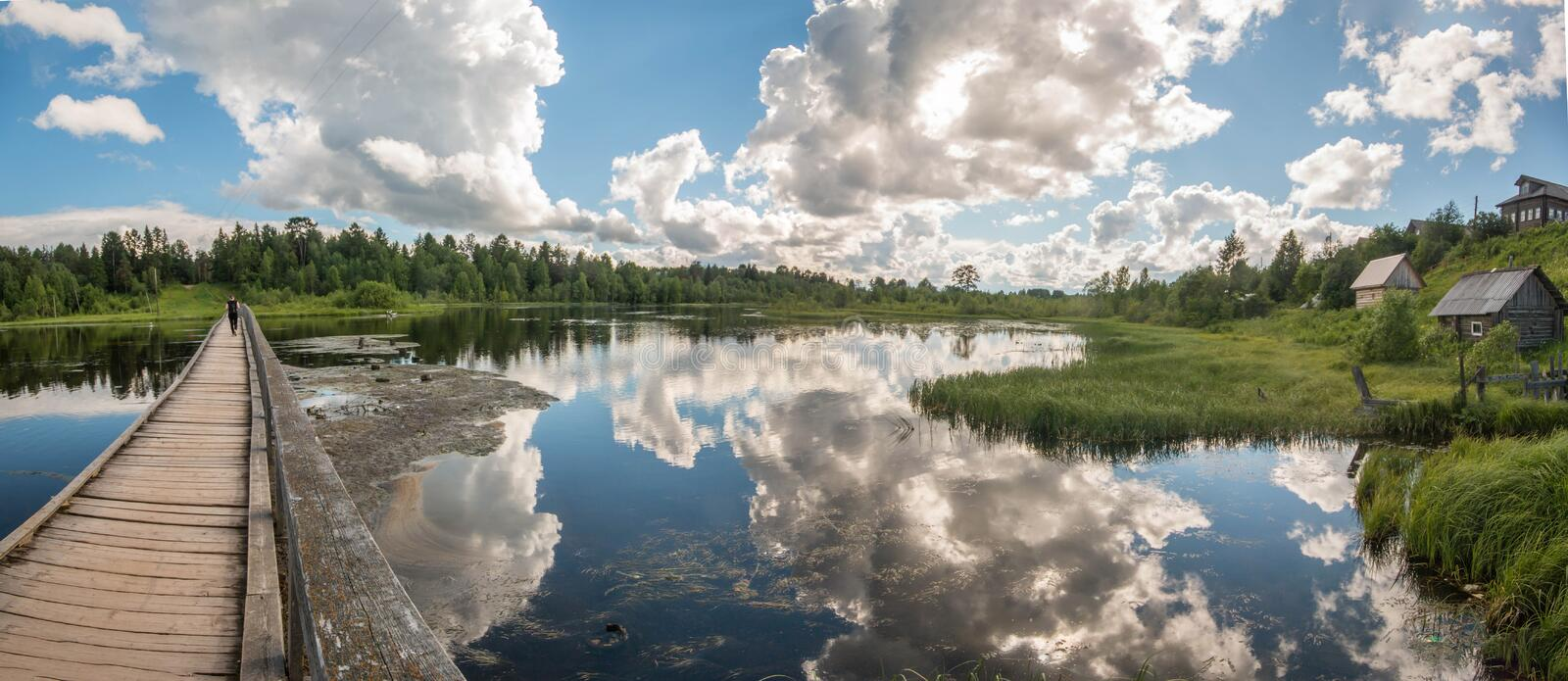North Russian village Isady. Summer day, Emca river, old cottages on the shore, old wooden bridge and clouds reflections. North Russian village Isady. Summer royalty free stock photo