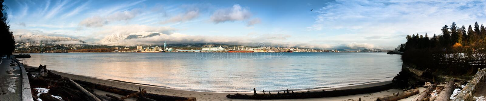 North Vancouver Shoreline Panorama. Panorama of North Vancouver industrial shoreline and ocean inlet looking over beach from Stanley Park, Vancouver royalty free stock images