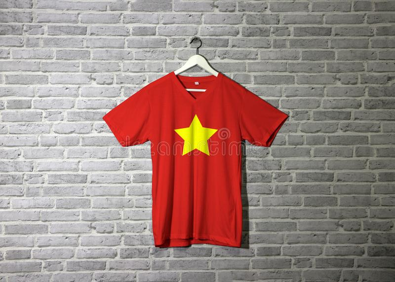 North Vietnam 1945 to1955 flag on shirt and hanging on the wall with brick pattern wallpaper. Flag of Democratic Republic of Vietnam yellow star on red stock image