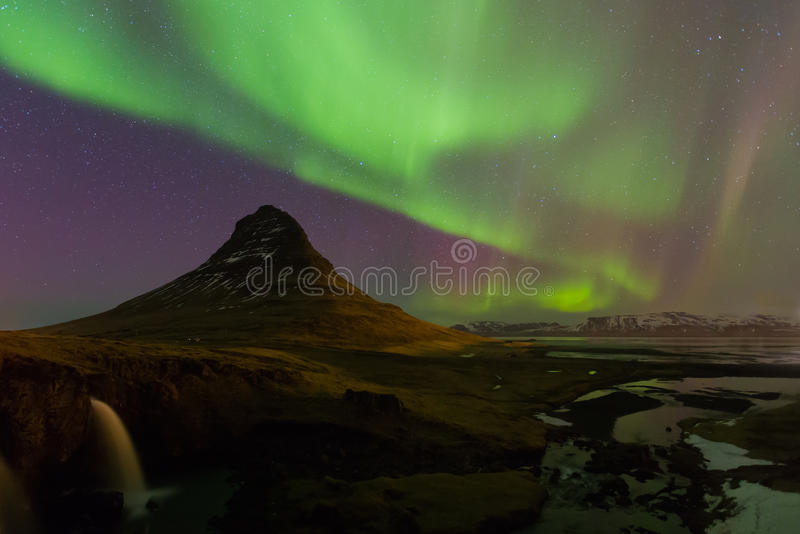 Northen lights over Kirkjufell mountain. Beautiful aurora over Kirkjufell mountain in Iceland with fully of star on sky royalty free stock photo