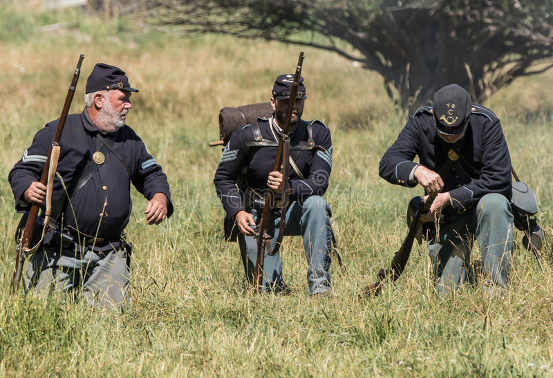 Northern Army Infantry. Portola, California, United States-July 4, 2015: Union infantry fire their muskets and reload during a skirmish with Confederate soldiers stock photography