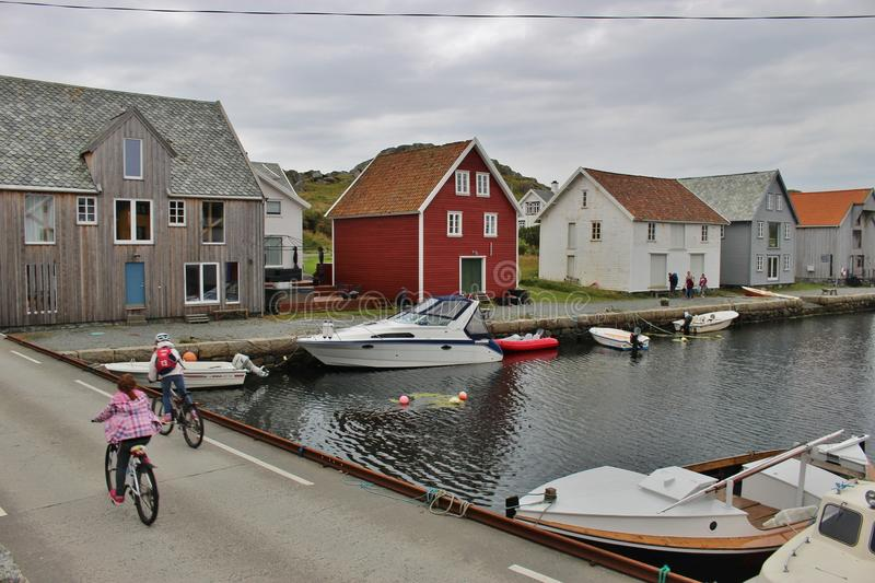 The Northern harbor of Utsira, Norway. UTSIRA, NORWAY – AUGUST 6, 2015: The Northern harbor of Utsira, Norway. Two girls ride down from a Ferry on their stock photography