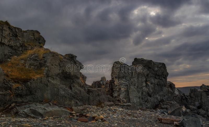 Northern landscape. Rocks against the dark dramatic sky. royalty free stock images