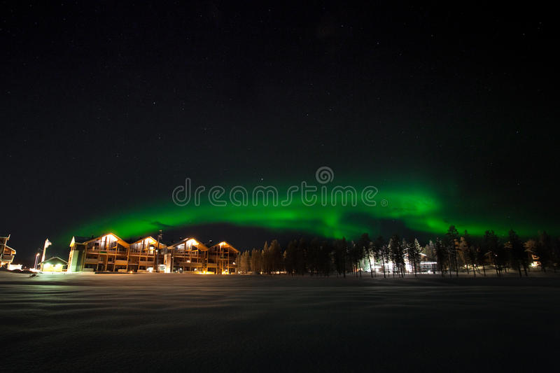 Northern light (Aurora Borealis). Witnessing green Northern light (Aurora Borealis) above hotel in Levi, Lapland, Finland stock image