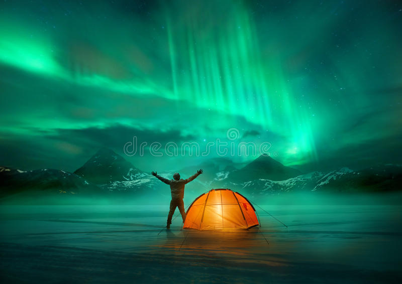Northern Lights Adventure. A man camping in wild northern mountains with an illuminated tent viewing a spectacular green northern lights aurora display. Photo stock images