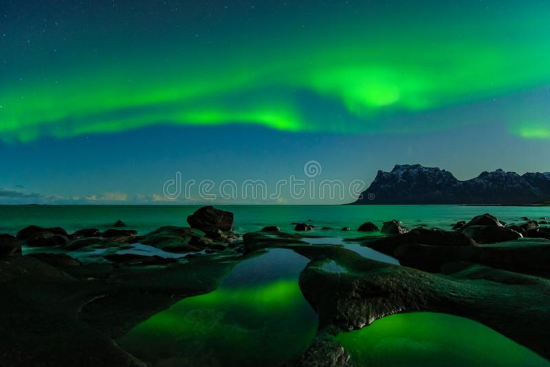 Northern lights, Aurora Borealis, with the Dragon Eye in the foreground, Uttakleiv Beach, Lofoten, Norway stock images