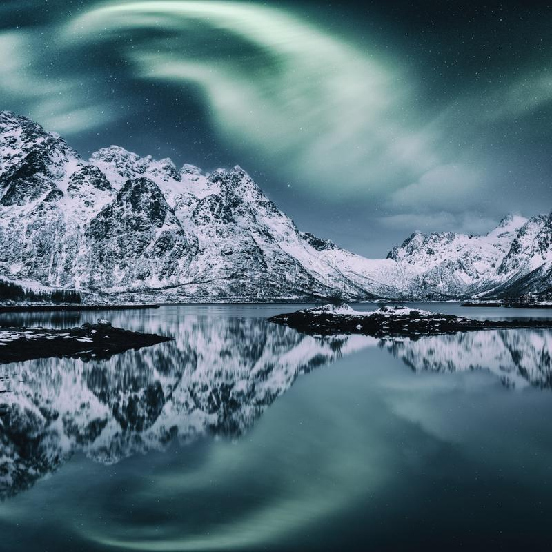 Northern lights, Aurora borealis, Lofoten islands, Norway. Night winter landscape with polar lights, starry sky and mountains stock image