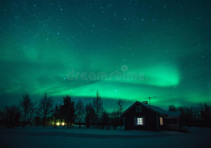 Northern lights Aurora Borealis over cottage in Lapland village. Finland royalty free stock photos