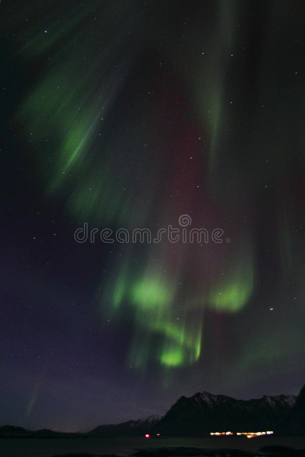 Northern Lights curtains over Brenna. Northern Light mirroring in the fjord facing the small village of Brenna, Lofoten islands royalty free stock images