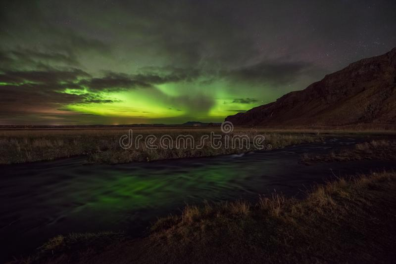 Aurora Borealis reflecting in a stream in Iceland royalty free stock photos