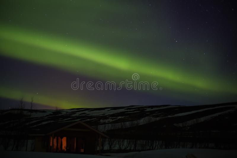 Northern lights with hut or bungalow. Northern lights with hut, trees and snowy mountains in iceland royalty free stock photography