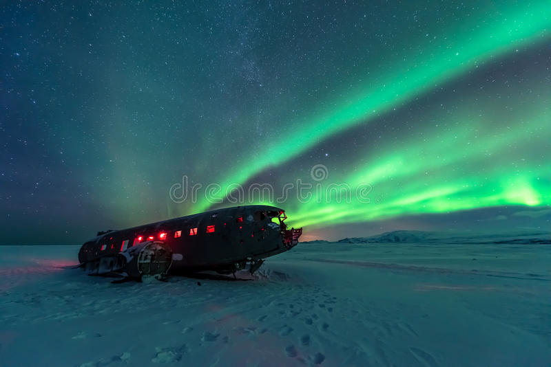 Northern lights over plane wreck on the wreck beach in Vik, Iceland. Northern lights over plane wreck stock photography