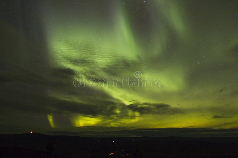Northern lights under clouds royalty free stock photography