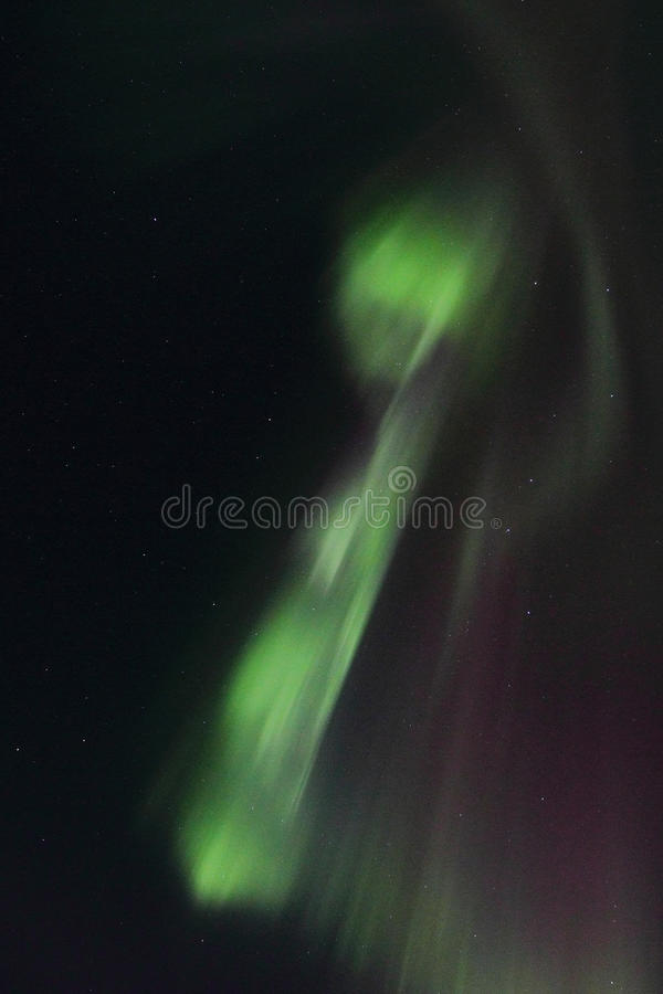 Northern Lights whirlpool over Gimsoey. Northern Light mirroring in the fjord facing Gimsoey, Lofoten islands royalty free stock photography