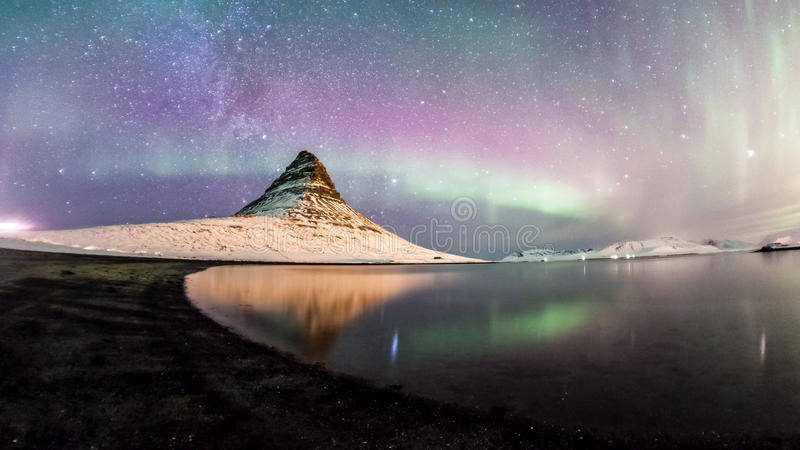 The Northern Lights and winter milky way over Kirkjufell. Colorful Aurora Borealis or better known as The Northern Lights and winter milky way over Kirkjufell royalty free stock image