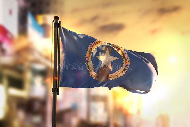 Northern Mariana Islands Flag Against City Blurred Background At. Sunrise Backlight Sky stock image