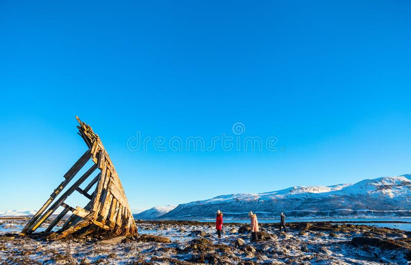 Northern Norway. Family of mother and kids exploring shipwrecked wooden viking boat in Northern Norway stock photo