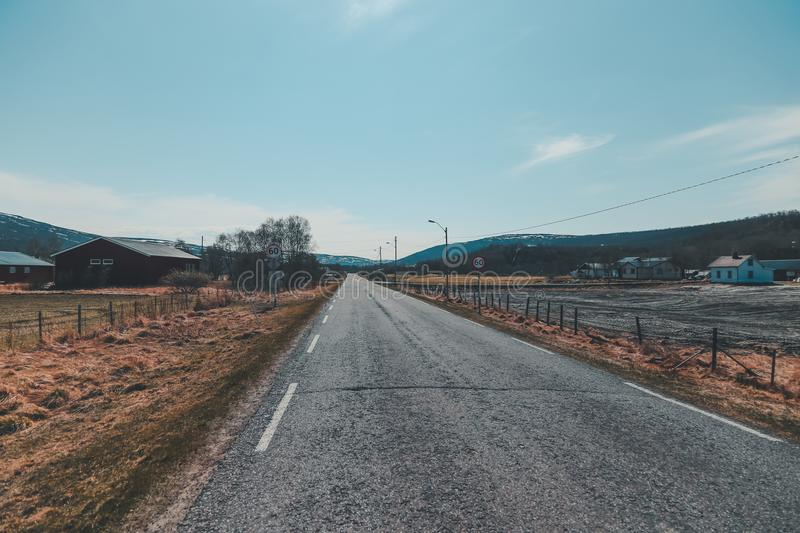 Norway, straight road in the countryside in the north on a sunny day. Northern Norway, straight road in the countryside in the north on a sunny day stock images
