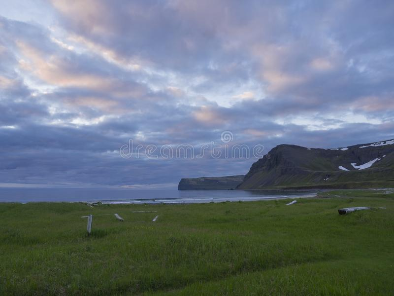 View on beautiful cliffs in Hloduvik cove in west fjords nature reserve Hornstrandir in Iceland, with green meadow, sea shore beac royalty free stock image