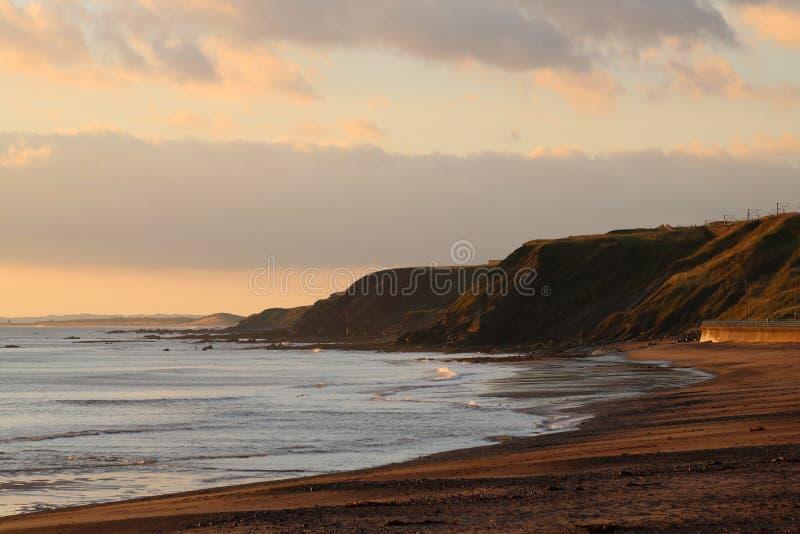 Northumberland kustlinje och klippor på soluppgång arkivbilder