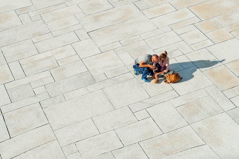 Noruega, Oslo 1 de agosto de 2013: Dos turistas de la gente joven relajar y ver las fotos en la costa del teatro de la ?pera en O imagen de archivo libre de regalías