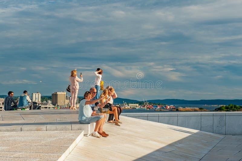 Noruega, Oslo 1 de agosto de 2013: Los turistas toman las fotos y admiran la vista del panorama de Oslo del terrapl?n del teatro  fotos de archivo