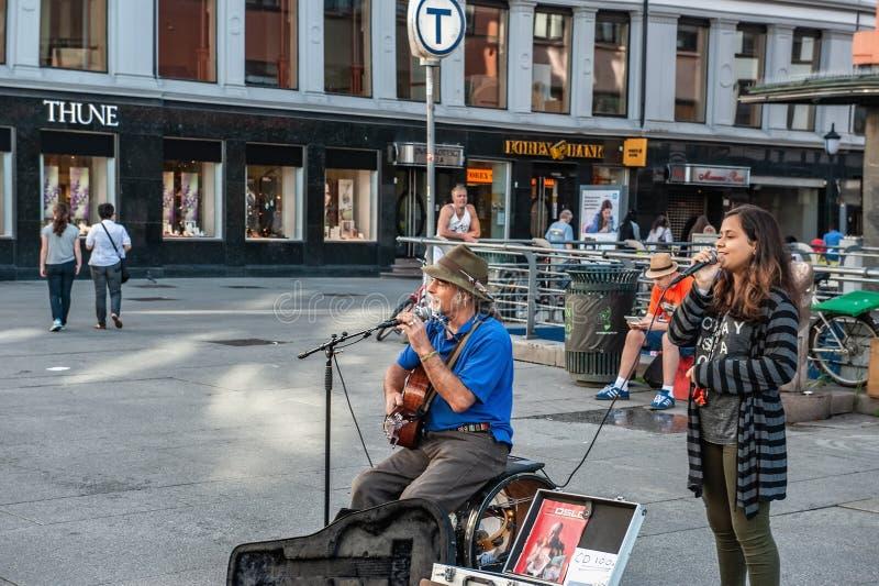 Noruega, Oslo 1? de agosto de 2013 M?sico e menina que cantam no quadrado em Oslo, a capital de Noruega Renda extra para fotografia de stock