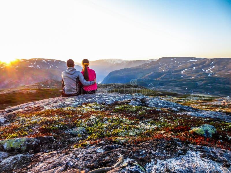 Noruega - um par que senta-se na rocha e que olha o por do sol fotografia de stock
