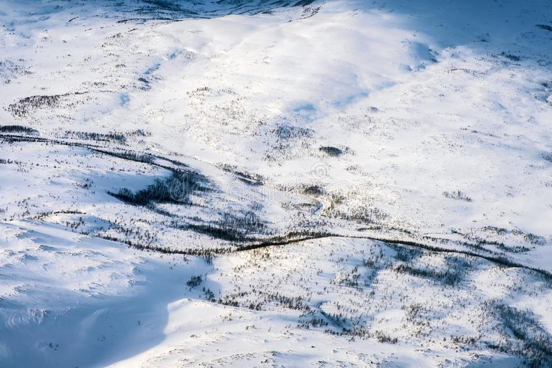 Aerial view of snowy landscape in winter with mountains and forest in Norway royalty free stock images
