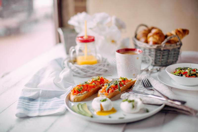 Norway breakfast. Toasts with salmon, boiled eggs on white wooden table with salad, coffee, orange juice and croissants stock image