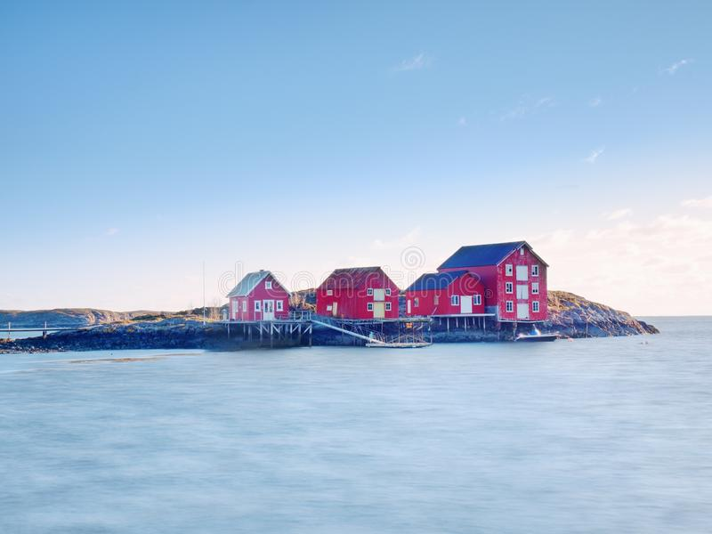 Norway fishing village on stony island. Shinning red white houses in quiet bay. Smooth water level mirroring stock photography