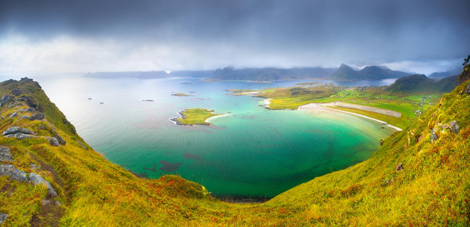 Norway landscape with fjord with emerald water. Panorama of lofoten islands coastline view from mountain peak. Soft green grass on hills and dramatic sky over stock image