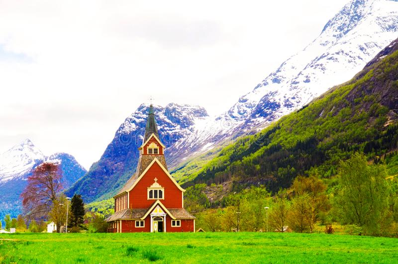 Norway Mountain Red Church, Religion and Faith, Travel Europe, Vikings. Horizontal photo of a Norwegian scenic landscape, with a small church and some snow in royalty free stock photos