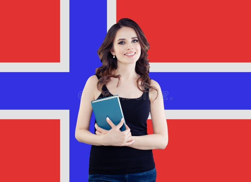 norway Studentessa graziosa allegra contro i precedenti della bandiera della Norvegia Viaggio ed imparare lingua norvegese fotografie stock