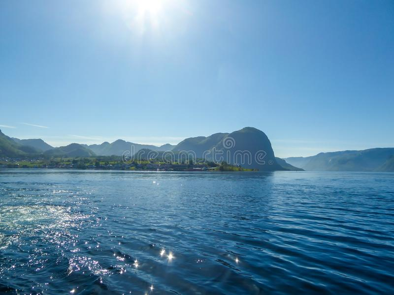 Norway - Sunny day over the fjord. A wast fjord near Rogaland, Norway. Water of the fjord is slightly wavy. Bright sunbeams reflect in the water`s surface. In stock images