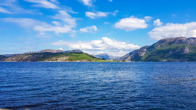 Norway - Sunny day over the fjord. A wast fjord near Rogaland, Norway. Water of the fjord is slightly wavy. Bright sunbeams reflect in the water`s surface. In royalty free stock photo