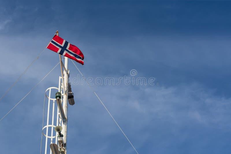 Norweg flaga przeciw niebieskiemu niebu fotografia stock