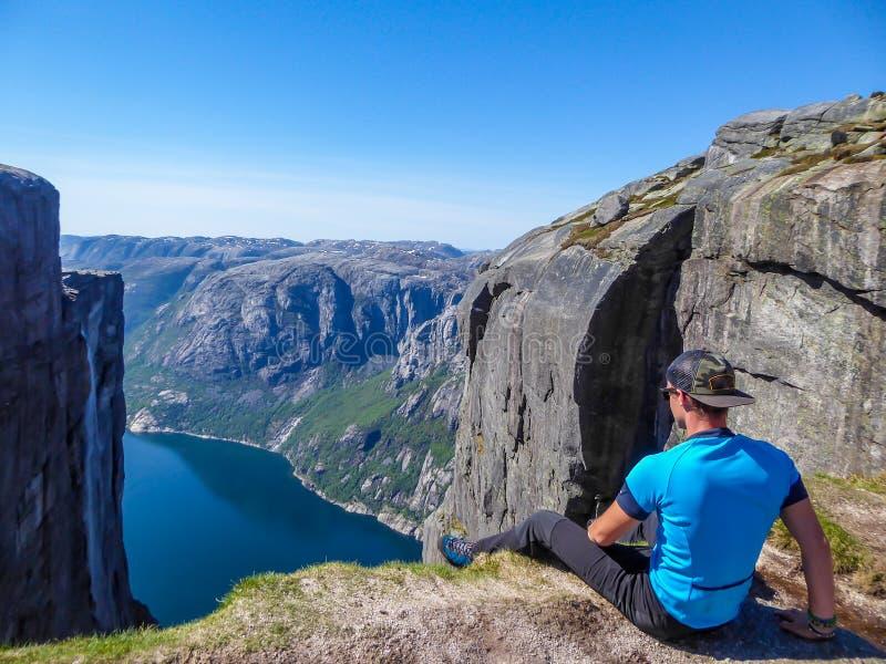 Norwegen - ein Mann, der am egde eines steilen Berges mit einer Fjordansicht sitzt lizenzfreie stockfotos