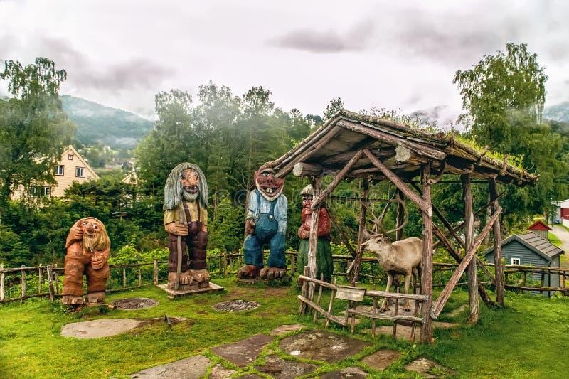 Norweger schnitzte hölzerne Skulpturen von Schleppangeln und ein Ren auf einem Hintergrund von Bergen am nebelhaften Morgen Skand stockbild