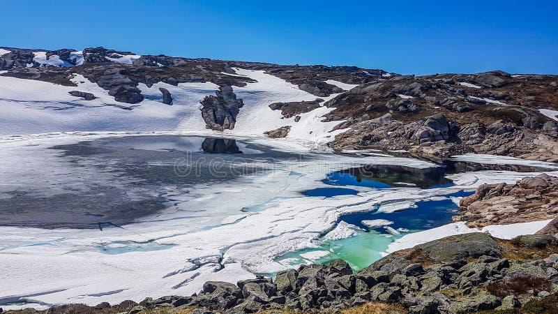 Norwegia - jezioro zakrywający z łupanie śniegiem i lodem obrazy royalty free