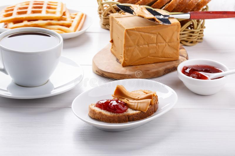 Norwegian brunost on white table. Breakfast with Scandinavian brown cheese, bread and coffee stock images