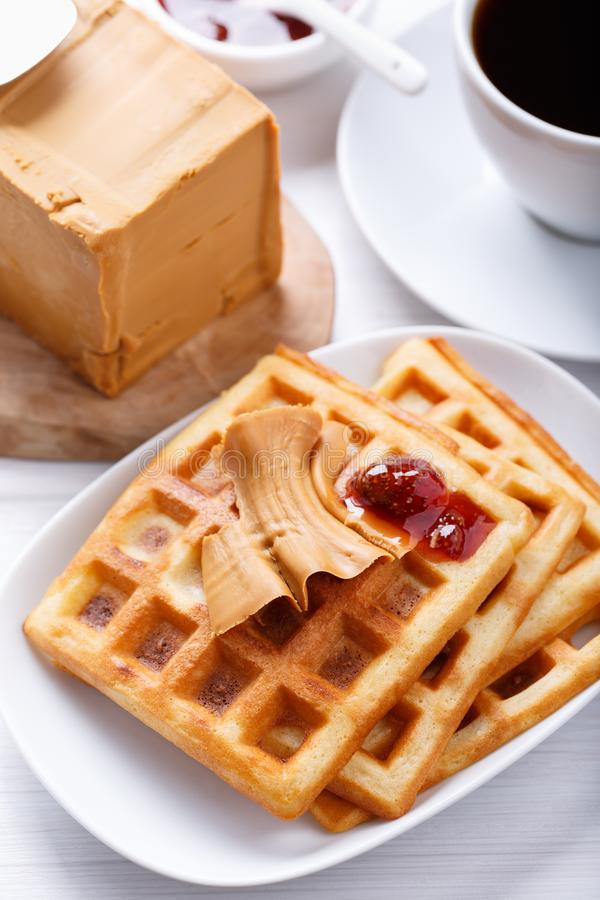 Norwegian brunost on white table. Breakfast with Scandinavian brown cheese, homemade waffles and coffee royalty free stock photography