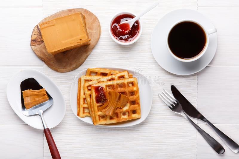 Norwegian brunost on white table. Breakfast with Scandinavian brown cheese, homemade waffles and coffee. Top view royalty free stock photo